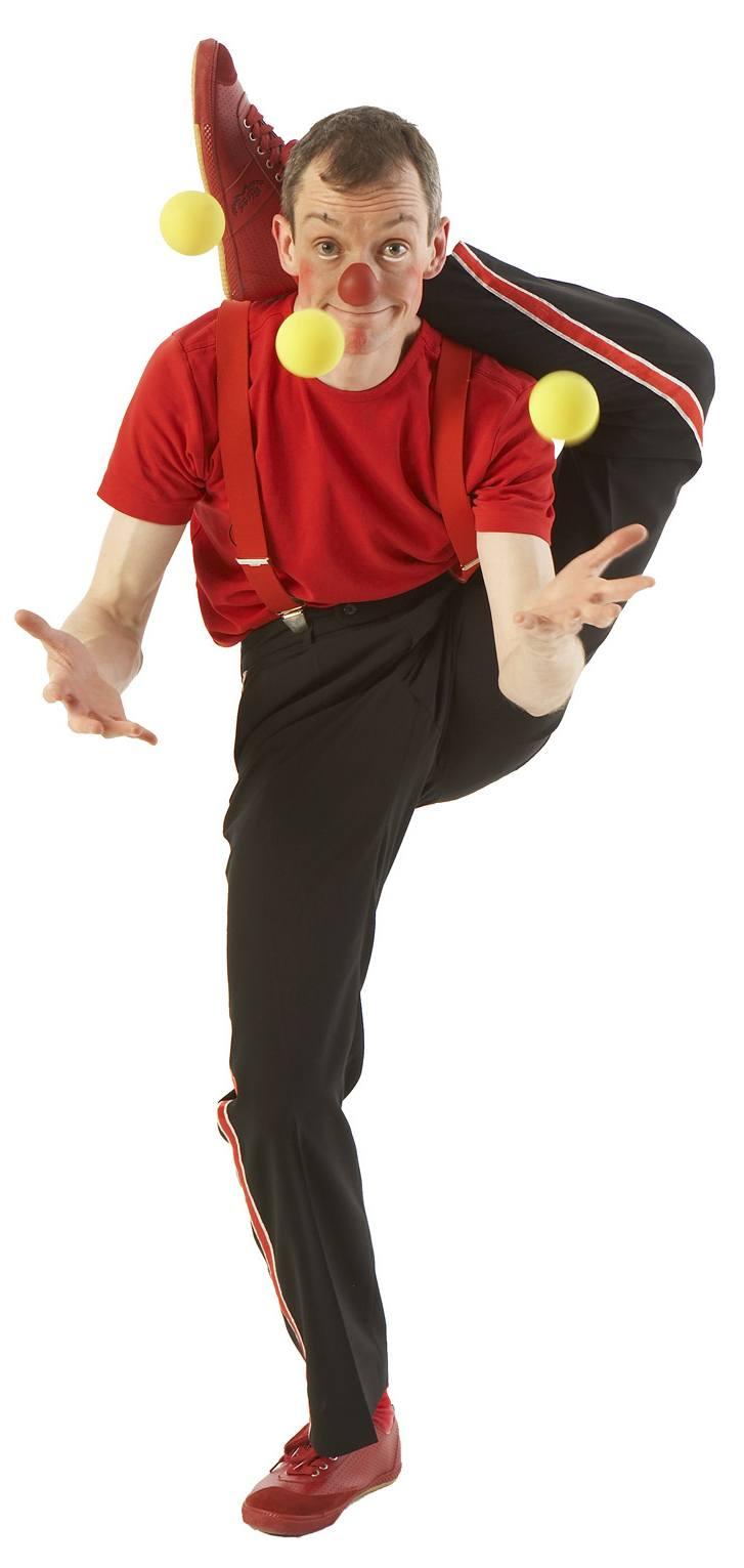 Klovnen Tapé jonglerer stående med det ene ben bag nakken