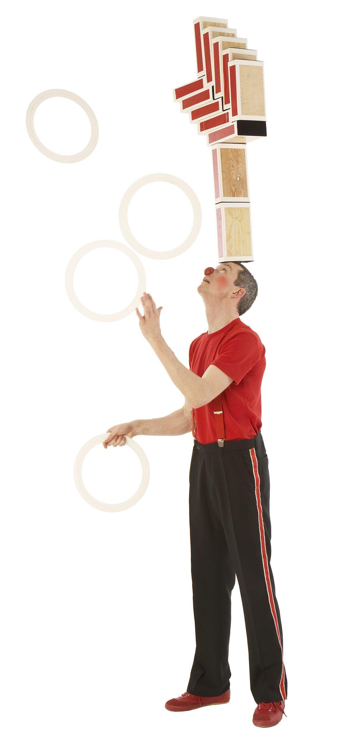 Klovnen Tapé jonglerer med ringe og balancerer 12 cigarkasser på panden samtidigt